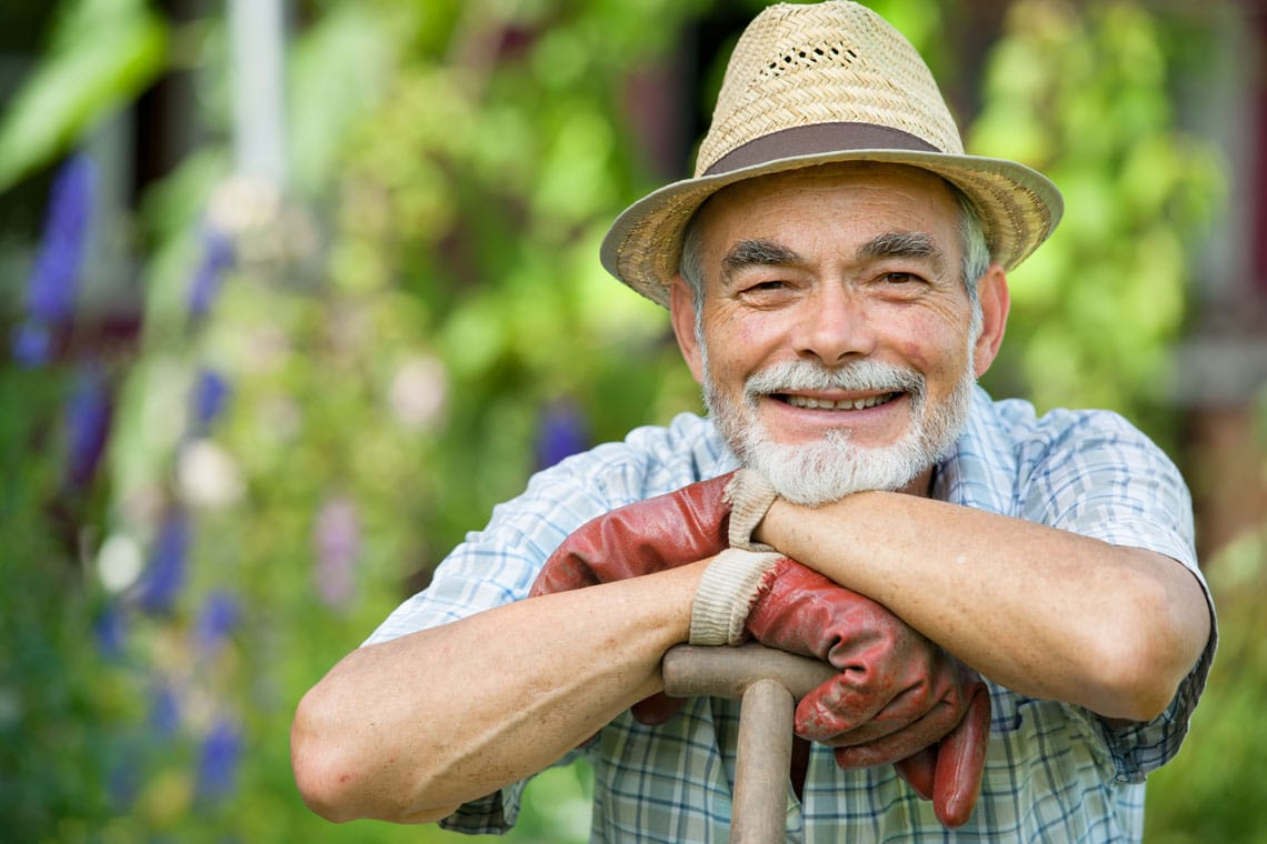 Fröhlicher Herr beim Gärtnern