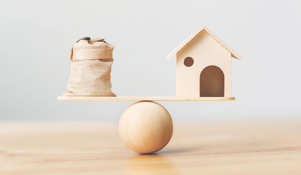 Holzhaus und Münzen auf Holzwaage