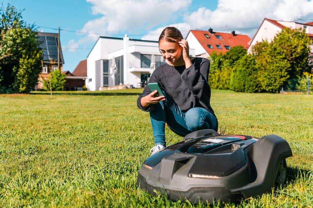 Frau steuert Roboter Rasenmäher