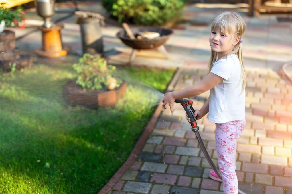 Kleinkind bei Gartenbewässerung